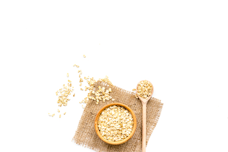 Cook oatmeal. Cereals in bowl and spoon on white background top view.