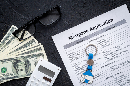 Housing loan. Draw up a mortgage. Mortgage application near keychain in shape of house and money on black background top view.