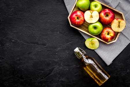 Bottle of fresh cider near autumn apples. Black background top view. Archivio Fotografico