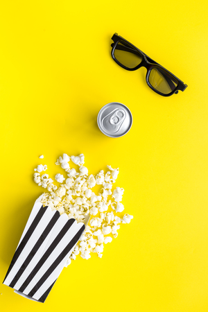 Cinema snacks. Popcorn in paper bag and soft drink near glasses on yellow background top view.