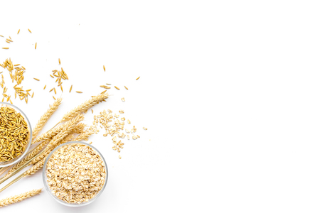 Oatmeal and oat in bowls near sprigs of wheat on white background top view. Stockfoto