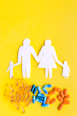 Prevention of diseases. Medicine for family health. Color pills near silhouette of family on yellow background top view.