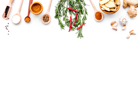 Seasoning background. Dry spices near ginger, garlic, rosemary on white background top view. Stockfoto