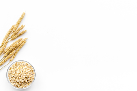 Cereals concept. Oatmeal in bowl near sprigs of wheat on white background top view.