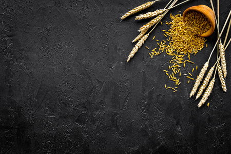 Raw oat in bowl near ears of wheat on black background top view. 版權商用圖片