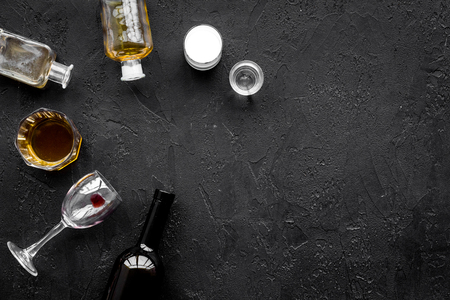 Alcohol abuse. Drunkennes. Glasses and bottles on black background top view.
