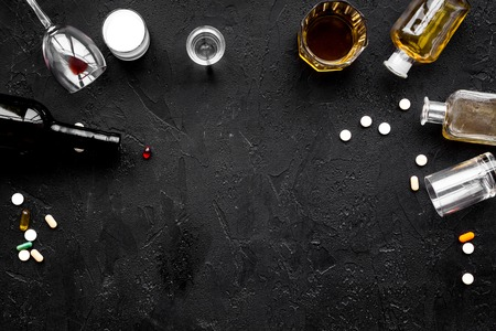 Alocohol abuse and alcoholism treatment concept. Glasses, bottles and medcine pills on black background top view. Stock Photo