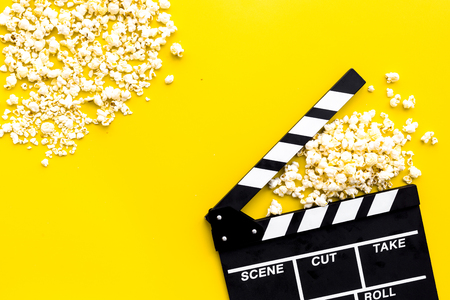 Cinema background. Film watching. Popcorn and clapperboard on yellow background top view copy space Stockfoto