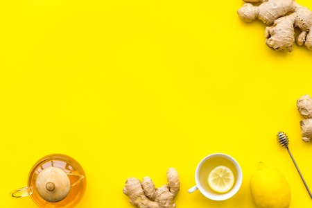 Warming tea with lemon and ginger. Cup, teapot, ginger root on yellow background top view copy space Stock Photo