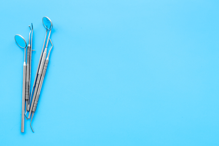 Dentist tools. Teethcare, dental health concept. Blue background top view copy space
