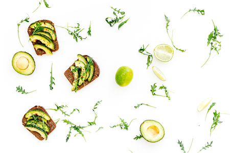 Have a bite with healthy snacks. Avocado toast on white background top view.