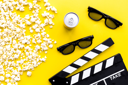 Cinema background. Glasses, popcorn and clapperboard on yellow background top view. Stock Photo