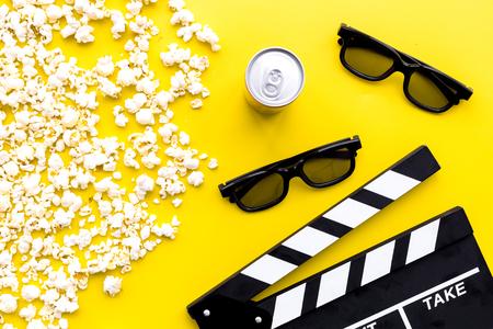 Sfondo cinema. Vetri, popcorn e ciak sulla vista superiore del fondo giallo.