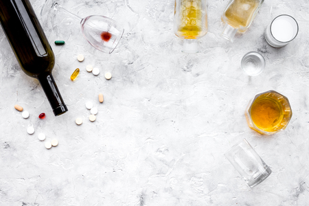 Alocohol abuse and alcoholism treatment concept. Glasses, bottles and medcine pills on light grey background top view. Stock Photo