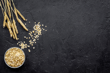 Cereals background. Raw oatmeal near sprigs of wheat on black background top view copy space