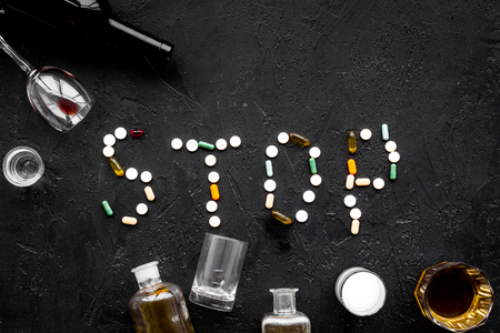 Stop alcohol. Word stop lined with pills near glasses and bottles on black background top view copy space