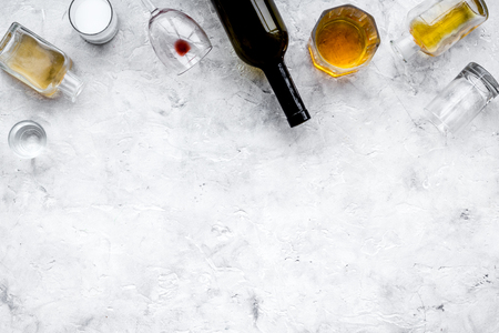 Alcohol abuse. Drunkenness. Glasses and bottles on grey background top view copy space