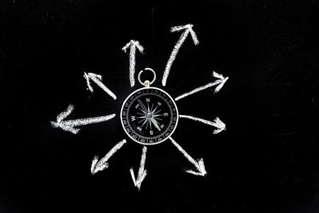Direction of movement, travel direction. Compass among the arrows on black background top view copy space