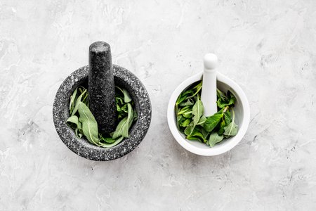 Phytotherapy. Herbs in mortar bowl on white background top view copy space