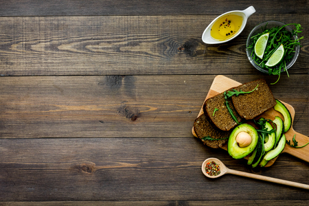 Breakfast for safety weight loss. Avocado toast with rye bread, lime, olive oil and greens on dark wooden background top view space for text Фото со стока