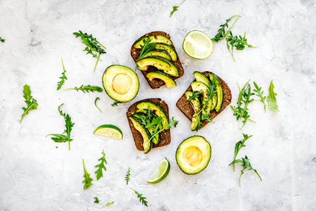Have a bite with healthy snacks. Avocado toast on grey background top view Banco de Imagens