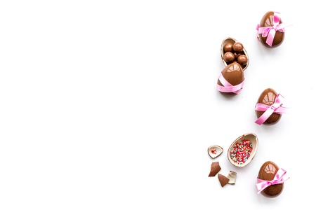 Sweets for Easter table. Chocolate eggs near cookies in shape of Easter bunny on white background top view copy space 写真素材