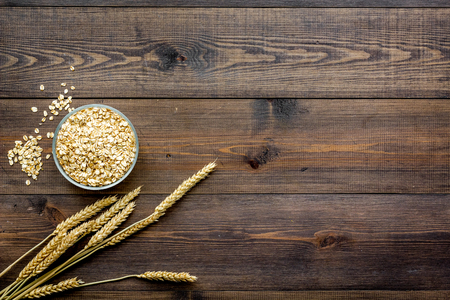 Cereals concept. Oatmeal in bowl near sprigs of wheat on dark wooden background top view copy space