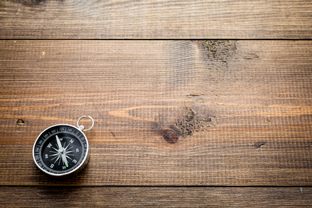 Compass on dark wooden background top view copy space