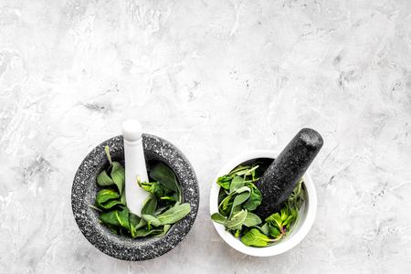 Harvest medicinal herbs. Greens in mortar bowl on grey background top view. 版權商用圖片