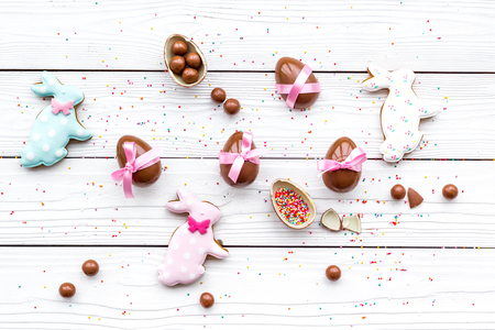 Celebrate Easter. Modern signs of Easter. Chocolate Easter eggs and Easter bunny cookies. White wooden background top view.