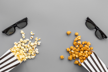 映画のコンセプトで映画を見る。灰色の背景の上のビューにポップコーンとメガネ。