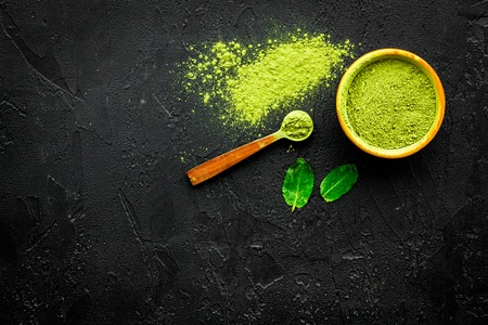Japanese traditional product. Matcha green tea in bowl and scattered on black background top view.