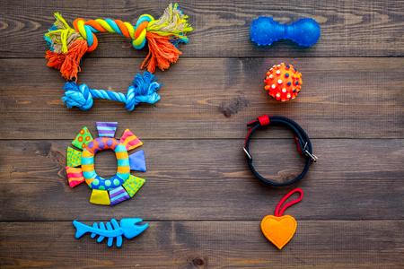 Pet accessories. Toys near collar on dark wooden background top view 版權商用圖片