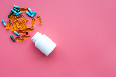 Color blue and yellow pills spilling out of a pill bottle on pink background top view.