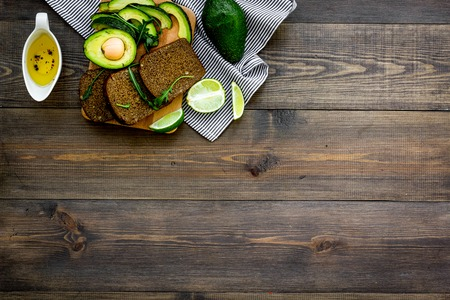 Breakfast for safety weight loss. Avocado toast with rye bread, lime, olive oil and greens on dark wooden background top view.
