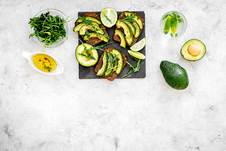 Snacks with avocado. Avocado toast with rye bread on grey background top view.