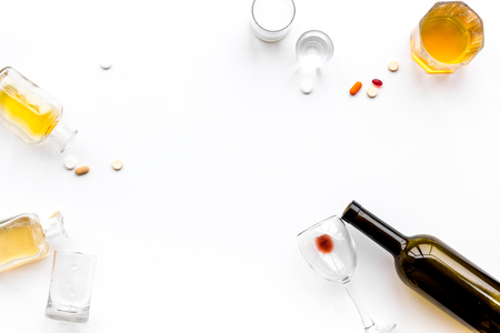Alocohol abuse and alcoholism treatment concept. Glasses, bottles and medcine pills on white background top view.