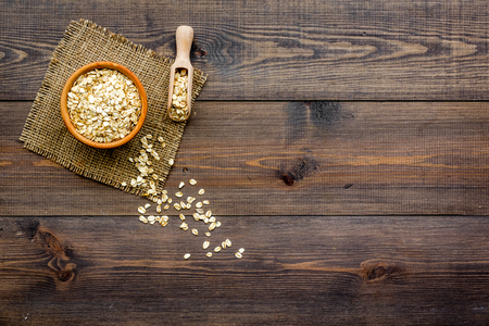 Cook oatmeal. Cereals in bowl and scoop on dark wooden background top view. Stock fotó