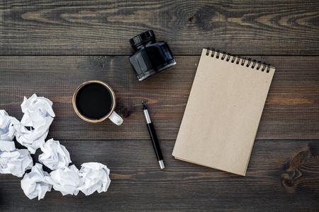 Writer profession. Retro concept. Notebook, pen, inkpot, coffee near crumpled paper balls on dark wooden background top view mock up Standard-Bild - 96050876