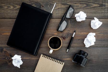 Writer profession. Retro concept. Notebook, pen, inkpot, coffee near crumpled paper balls on dark wooden background top view Standard-Bild - 96050878