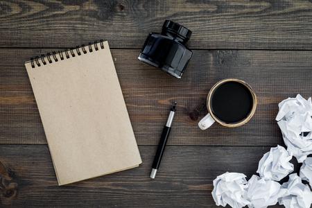 Writer profession. Retro concept. Notebook, pen, inkpot, coffee near crumpled paper balls on dark wooden background top view. Standard-Bild - 96192435