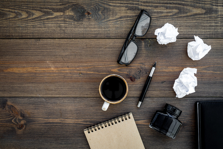 Writer profession. Retro concept. Notebook, pen, inkpot, coffee near crumpled paper balls on dark wooden background top view. Standard-Bild - 96192437