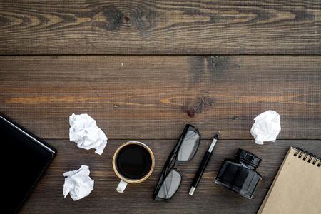 Writer profession. Retro concept. Notebook, pen, inkpot, coffee near crumpled paper balls on dark wooden background top view. Standard-Bild - 96192440