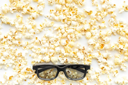 Cinema accessories. Cinema glasses and popcorn on white background top view.