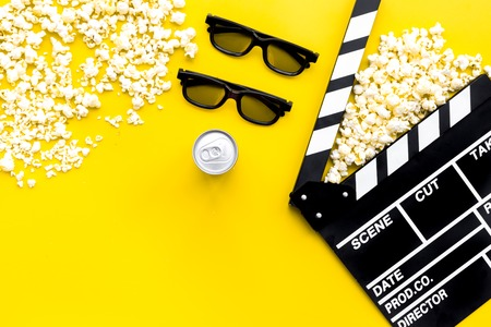 Cinema background. Glasses, popcorn and clapperboard on yellow background top view. 写真素材