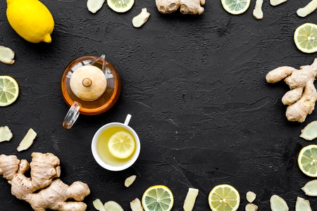 Tea for cure colds. Cup, teapot, ginger root and lemon on black background top view. Stock Photo