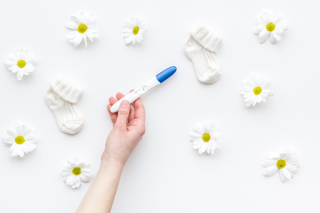 Joy of long-awaited pregnancy. Hand hold pregnancy test with two stripes near flowers and booties on white background top view