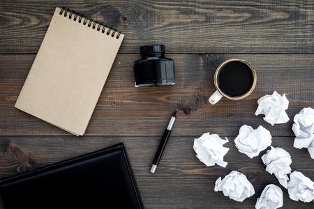 Writer profession. Retro concept. Notebook, pen, inkpot, coffee near crumpled paper balls on dark wooden background top view. Standard-Bild - 96270578