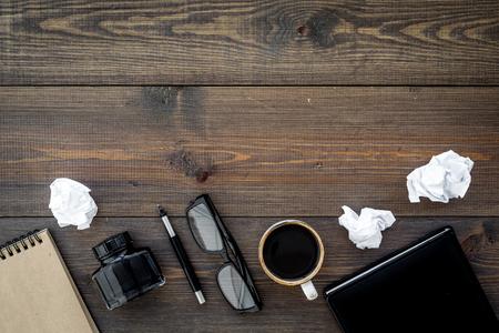 Writer profession. Retro concept. Notebook, pen, inkpot, coffee near crumpled paper balls on dark wooden background top view. Standard-Bild - 96270584