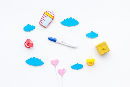 Pregnancy and preparation for childbirth. Pregnancy test near child accessories on white background top view.